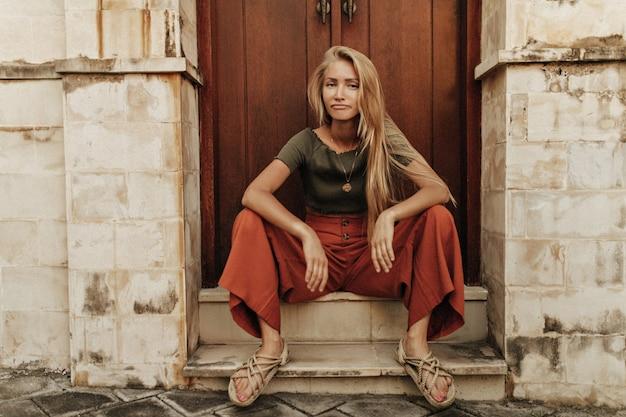 Raffreddare giovane bionda triste donna dai capelli lunghi in pantaloni rossi larghi e t-shirt cachi si siede in posa divertente vicino alla porta di legno e guarda in avanti