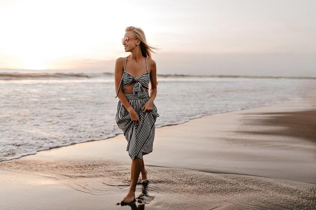 세련된 스트라이프 드레스와 분홍색 선글라스에 멋진 젊은 금발의 여자가 해변에 걸어 미소 짓고 일몰을 즐깁니다.