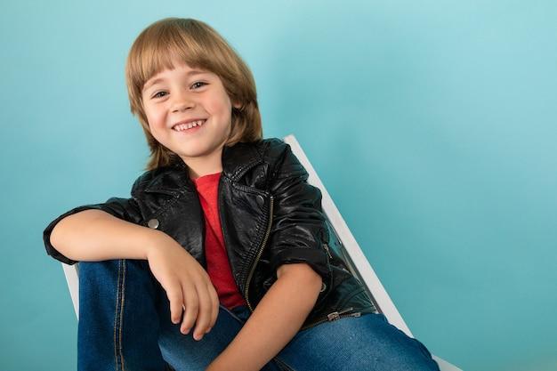 Прохладный мальчик в кожаной куртке на синем фоне студии.