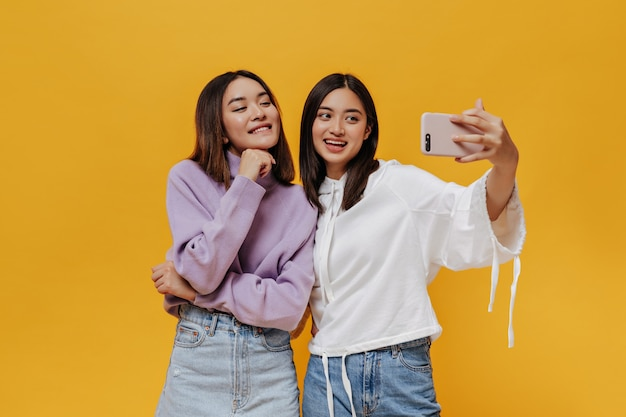 Cool young brunette asian women in stylish sweatshirts take selfie, smile sincerely and pose in good mood on orange wall