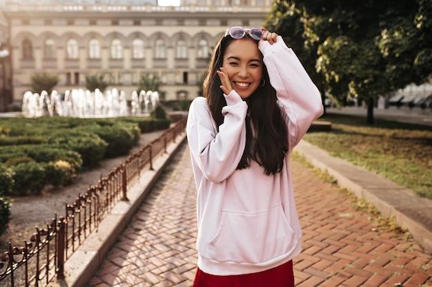 분홍색 후드티를 입은 멋진 젊은 브루네트 여성, 빨간 실크 치마는 진심으로 웃고, 행복해 보이며 밖에서 선글라스를 벗습니다.