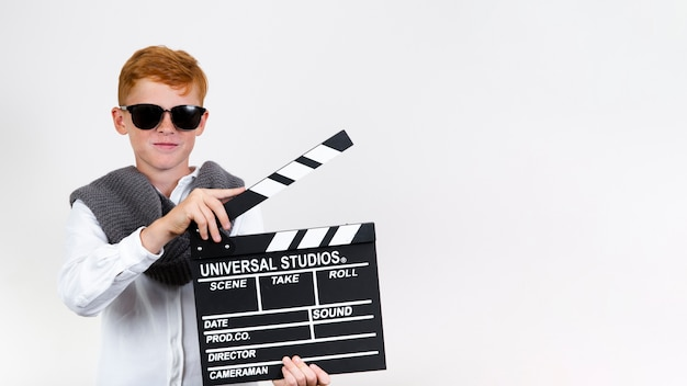 Cool young child holding clapperboard