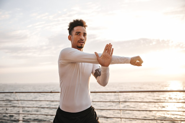 Cool young dark-skinned man in long-sleeved white t-shirt and black shorts stretches and works out near sea