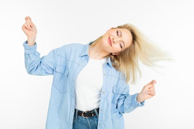 Крутая молодая энергичная девушка танцует на белом фоне студии