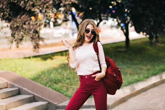 Крутая молодая девушка с бордовой сумкой и длинными вьющимися волосами веселится в парке в городе. она носит цвет марсала и выглядит взволнованной.