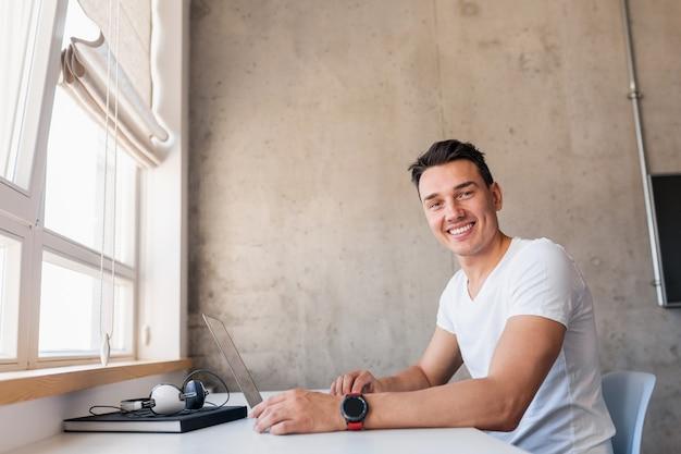 ラップトップに取り組んでいるテーブルに座っているカジュアルな服装でクールな若いハンサムな笑みを浮かべて男