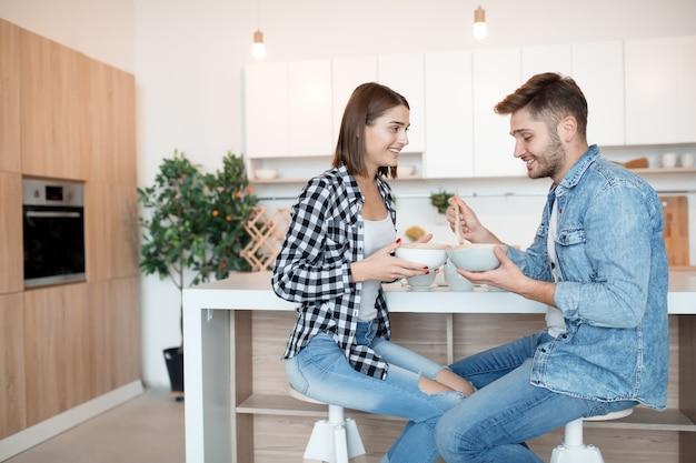 クールな若い幸せな男とキッチンで朝食、朝一緒にカップル、笑顔、話して女