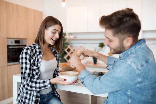 Прохладный молодой счастливый мужчина и женщина на кухне за завтраком, пара вместе утром, улыбаясь, разговаривая
