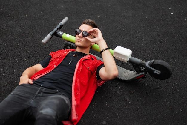 빈티지 청바지에 트렌디 한 헤어 스타일로 세련된 빨간 조끼에 멋진 젊은 힙 스터 남자가 거짓말을하고 세련된 선글라스를 곧게 만듭니다.