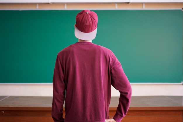 Cool young hipster student in snapback cap and casual in university with blackboard on background