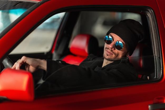 선글라스를 쓴 멋진 젊은 남성 운전자가 빨간 차를 운전하고 있습니다. 남자는 바퀴 뒤에 여행