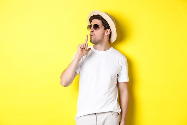 黄色の背景に立って、鉄砲のジェスチャーを吹いて自信を持って見えるクールな若い男性観光客。休暇とライフスタイルの概念