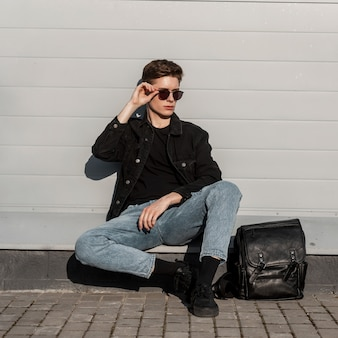 신발에 가죽 배낭과 세련된 블랙 데님 남성복에 멋진 젊은 남자