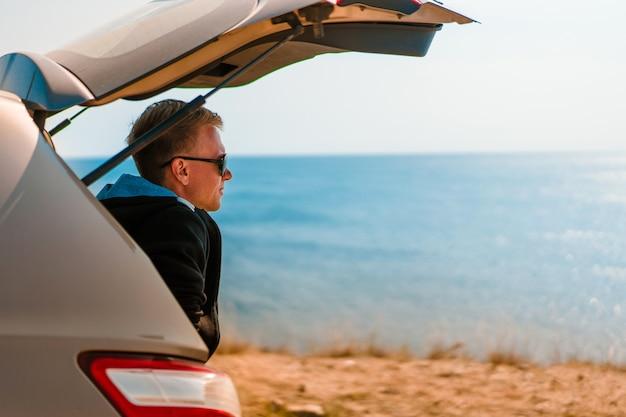 サングラスをかけたクールな若い男が日没時の海の景色を望む車のトランクに座って、車の旅のコンセプト