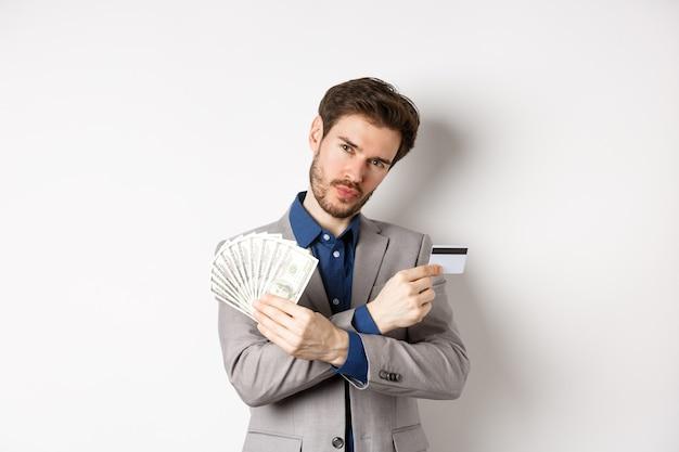 달러 지폐와 플라스틱 신용 카드를 보여주는 소송에서 멋진 젊은 부자, 돈을 버는, 흰색 배경에 서.