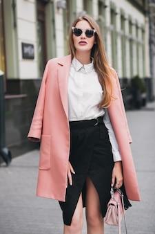 通りを歩いて、ピンクのコート、財布、サングラス、白いシャツ、黒のスカート、ファッション衣装、秋のトレンド、幸せな笑顔、アクセサリーを着てクールな若いスタイリッシュな美しい女性