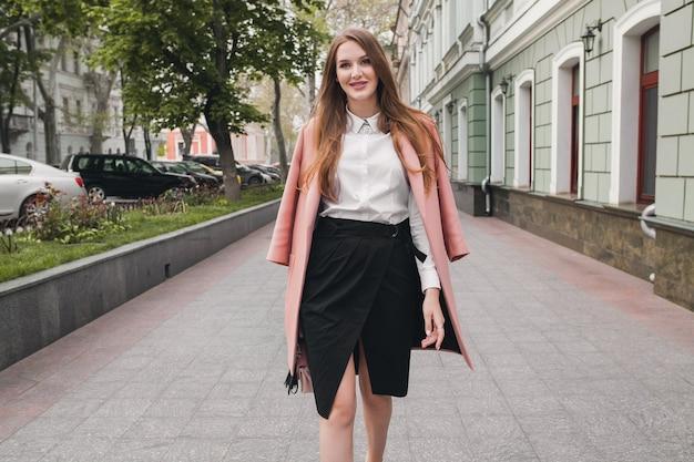 通りを歩いて、ピンクのコート、財布、白いシャツ、黒のスカート、ファッション衣装、秋のトレンド、幸せな笑顔、アクセサリーを着てクールな若いスタイリッシュな美しい女性