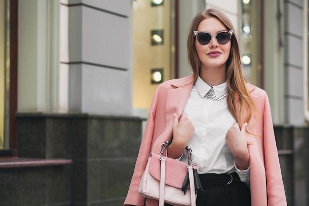 Raffreddare giovane bella donna alla moda che cammina per strada, indossa cappotto rosa, borsa, occhiali da sole, camicia bianca, gonna nera, vestito di moda, tendenza autunnale, sorridendo felice, accessori