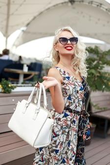 白いバッグとパターンのファッションドレスでサングラスをかけたクールな若いスタイリッシュな女の子が街を歩く