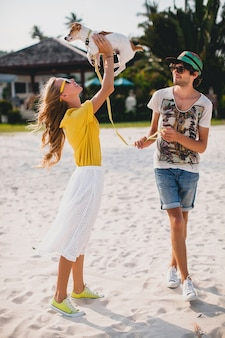 Крутая молодая стильная хипстерская влюбленная пара гуляет и играет с собакой на пляже