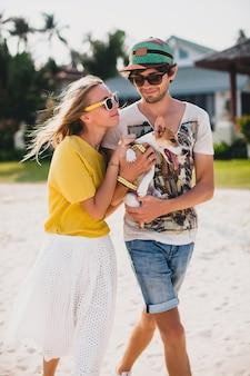 Прохладная молодая стильная хипстерская влюбленная пара гуляет, играя собачьим щенком джек рассел на тропическом пляже, белый песок, романтическое настроение, весело, солнечно, мужчина женщина вместе, отпуск