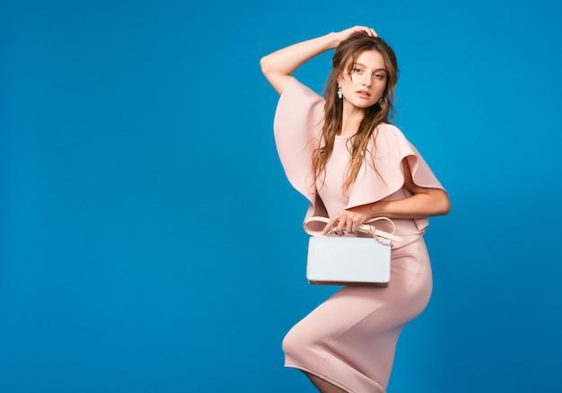 Крутая молодая стильная сексуальная женщина в розовом роскошном платье, тренд летней моды, шикарный стиль, держа модную сумочку