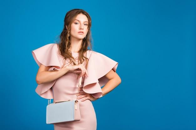 Raffreddare giovane donna sexy alla moda in abito di lusso rosa, tendenza moda estiva, stile chic, sfondo blu studio, tenendo borsa alla moda