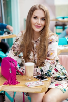Cool young stylish woman sitting in cafe