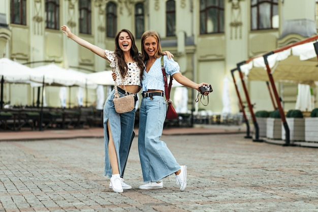 Cool young tanned girlfriends in trendy loose jeans and floral blouses hug outdoors