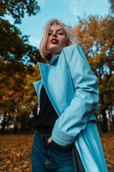 秋の公園を歩いているスタイリッシュな秋の青いロングコートを持つクールな若い流行モデルの女の子