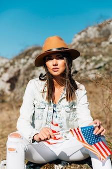 Крутая молодая женщина сидит на камне с флагом сша