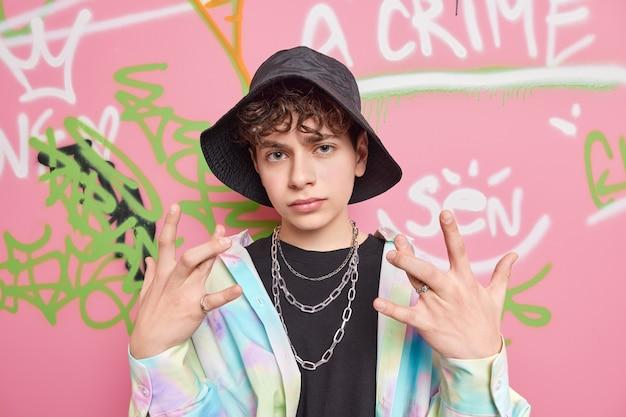巻き毛のクールな若者が指を交差させるジェスチャーは積極的に黒い帽子をかぶっていますカラフルなシャツメタルチェーンはカラフルな落書きの壁に対して若者のサブカルチャースタンドに属しています