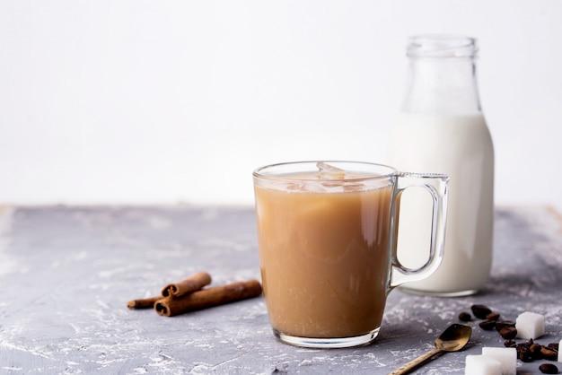 우유, 계 피 스틱, 커피 콩, 설탕, 테이블에 숟가락으로 커피를 냉각.