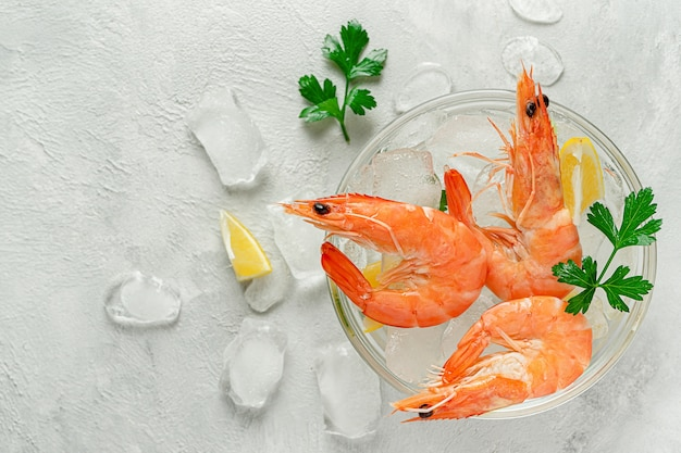 Охлажденные креветки в миске со льдом, лимоном и петрушкой на сером фоне. итальянская еда, копия пространства.