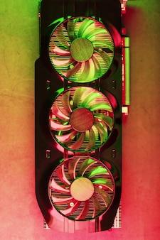 Кулеры игровой видеокарты в красном и зеленом неоновом свете. высокотехнологичный графический процессор для игр и майнинга крипто-ферм