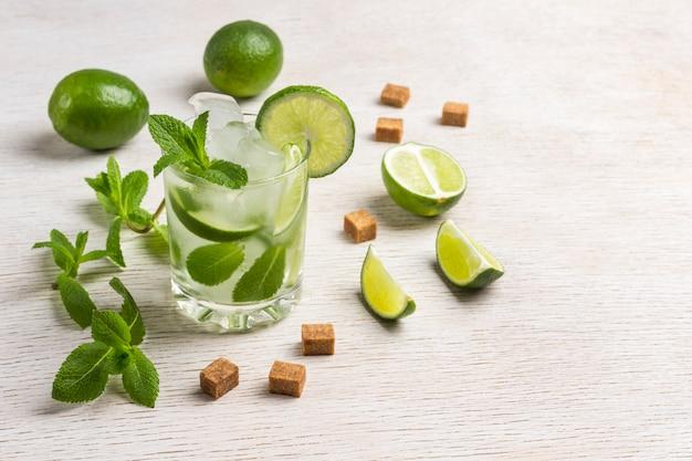 Охлаждающий напиток со льдом, лаймом и мятой. ломтики коричневого сахара, листья мяты, плоды лайма.