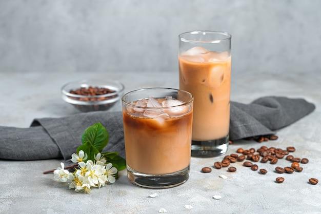 Охлаждение кофе со льдом в двух стаканах на серой стене. вид сбоку горизонтальный.