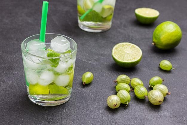 氷でレモン飲料を冷やす。ガラスのストロー。テーブルの上のライム。黒の背景。上面図