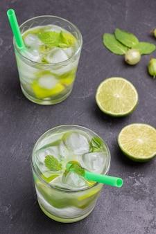 氷でレモン飲料を冷やす。ガラスのストロー。テーブルの上のライムの2つの半分。黒の背景。