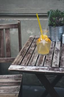 Cooling orange lemonade on a wooden desk outside
