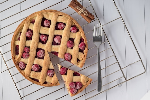 Cooling rack with delicious raspberry pie on white wooden table, top view
