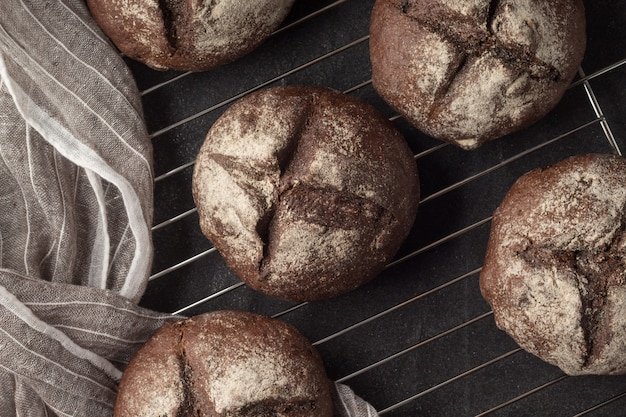 Cooling rack with fresh homemade rye buns on grey background, top view