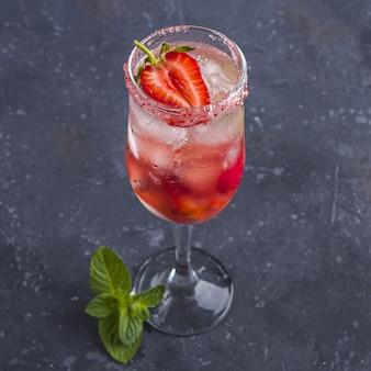 Охлаждающий итальянский алкогольный коктейль россини с игристым вином, клубникой, кубиками льда в бокале с шампанским