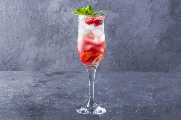 シャンパングラスのワイン、イチゴ、アイスキューブでイチゴサングリアを冷却