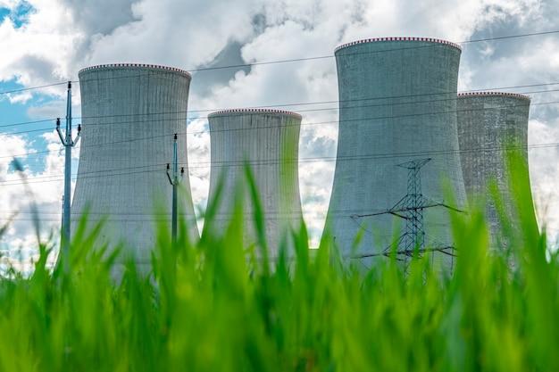 Градирня атомной электростанции за зеленой травой атомной энергии ядерной энергии и окружающей среды