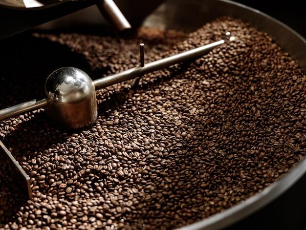 茶色の焙煎コーヒー豆が入った冷却トレイ