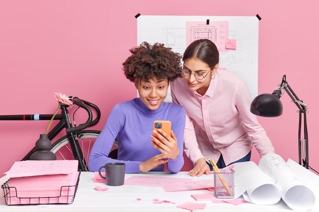 협력 및 팀워크 개념. 전문 두 여성 동료가 셀룰러를 확인하고 새 집에 대한 청사진 작업 또는 데스크톱에서 사무실에서 포즈를 취합니다.