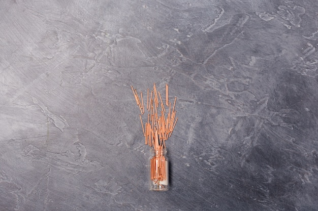 Cooper metal nails from glass bottle on grey backgrounds, tools construction equipment concepts. free space. copy space.