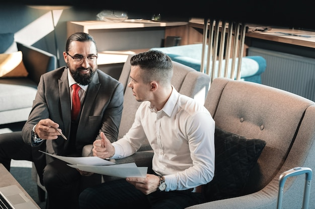 Cooperating with boss. dark-haired young assistant feeling happy while cooperating with his bearded boss