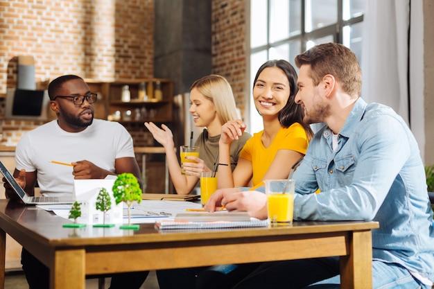 공부에 협력. 의사 소통을하고 음료를 즐기면서 테이블에서 휴식을 취하는 네 명의 활기차고 잠겨있는 행복한 학생